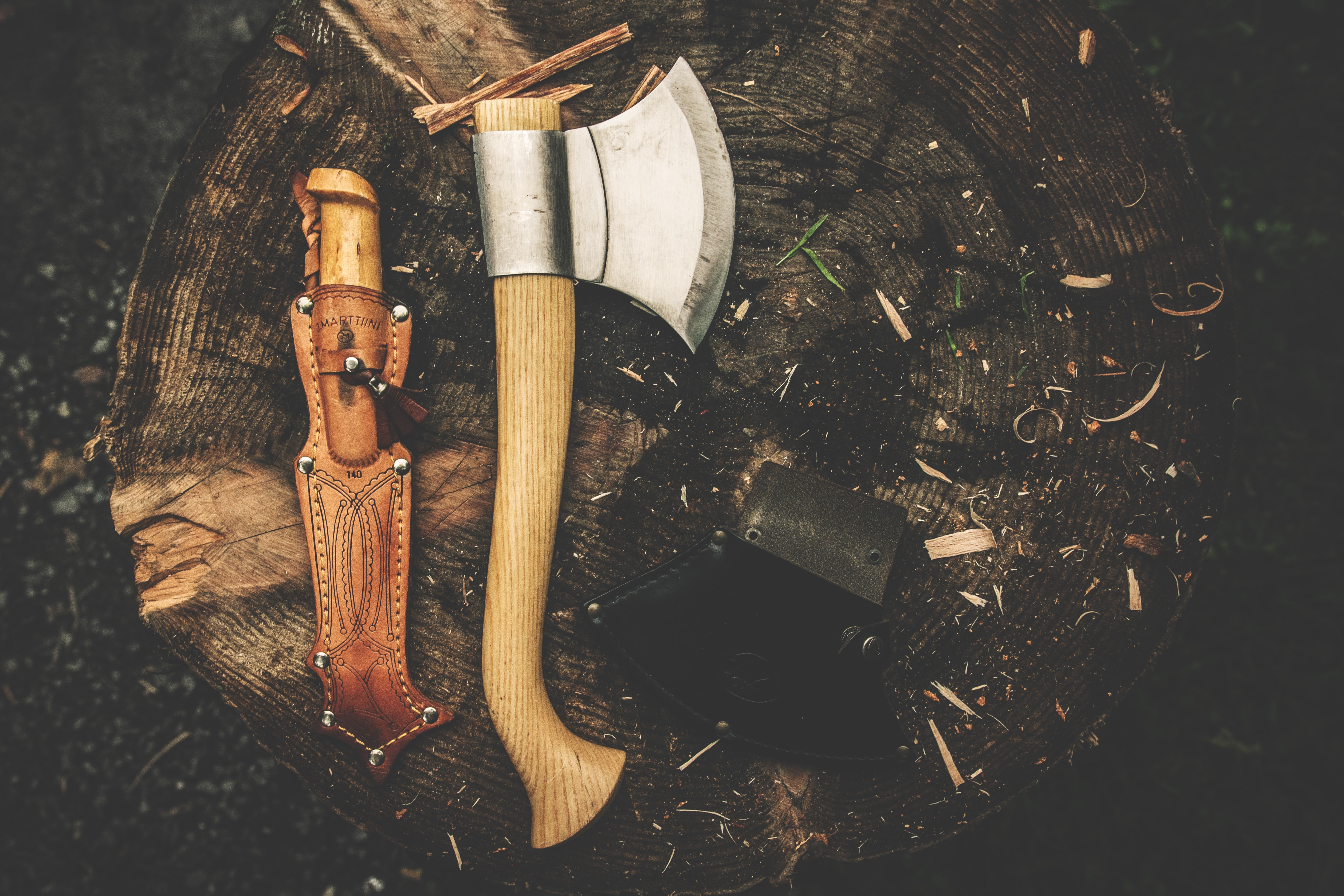 A bushcraft knife and an axe laying on a tree stump